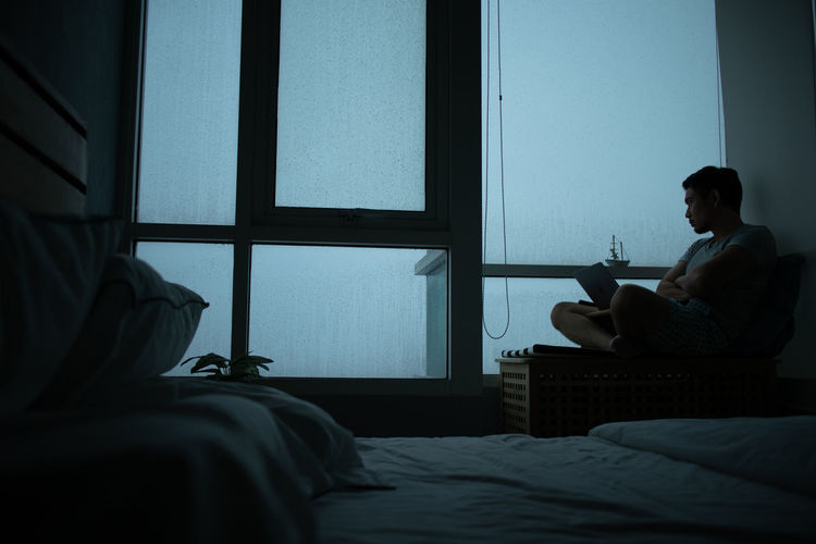 Depressed man sitting by window at home