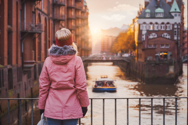 Rear view of woman standing by railing in city during winter
