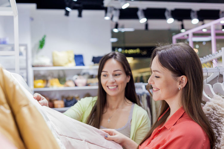 Close-up of smiling women standing in clothing store