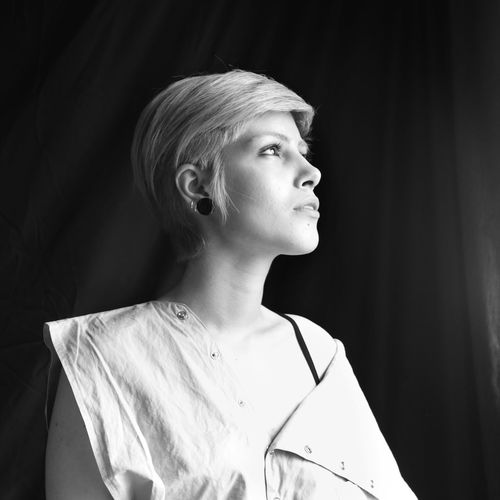 Low angle view of thoughtful mid adult woman looking away while standing in darkroom