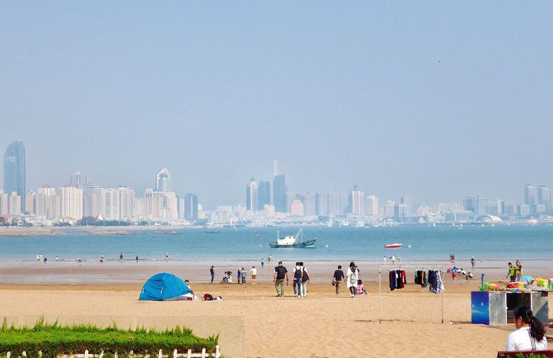 People at beach with city in background