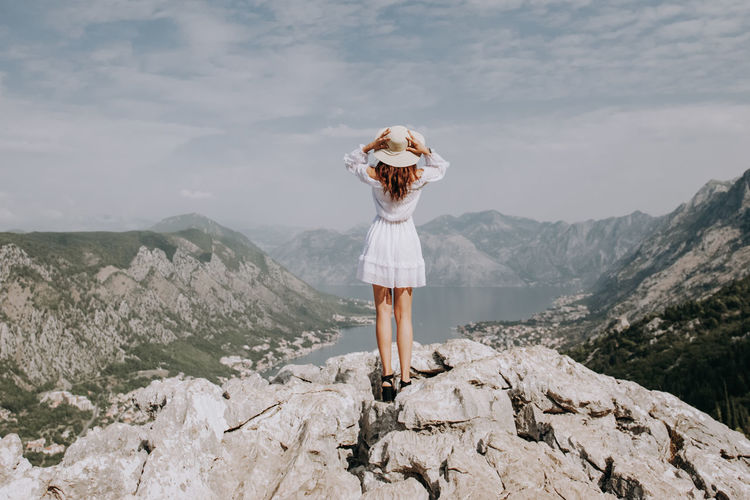 Woman standing on rock by mountains against sky