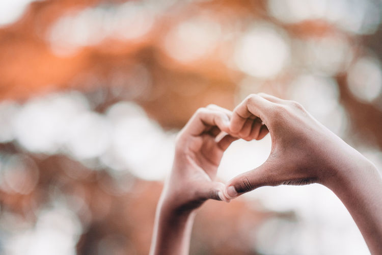 Close-up of person hand making heart shape outdoors