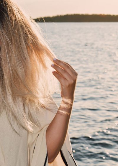 Close-up of woman with blond hair at sea