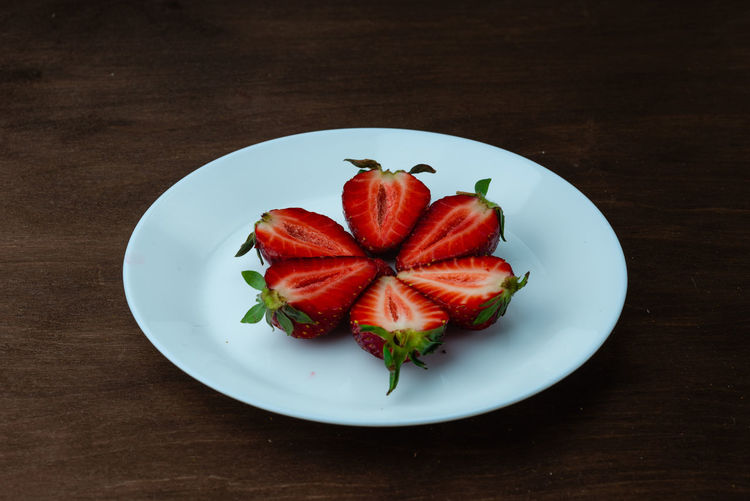 Strawberries on a white plate on a wooden table. creeative background concept. Food And Drink Food Freshness Red Indoors  Still Life No People Strawberry Strawberries Fruit Fruits Fresh Healthy Eating Vehetable Natural Raw Vitamin Raw Food Tasty Breakfast Ripe Juicy Sweet Berry Delicious Nutrition Background Rustic Dessert Freshness Eating Organic Close-up Diet Ingredient Vegan Snack Apperitive Pattern Dark Wooden Table Brown Texture Textured  Bowl Plate Ceramic Wellbeing Directly Above Berry Fruit High Angle View Ready-to-eat Wood - Material Serving Size Herb Garnish Mint Leaf - Culinary
