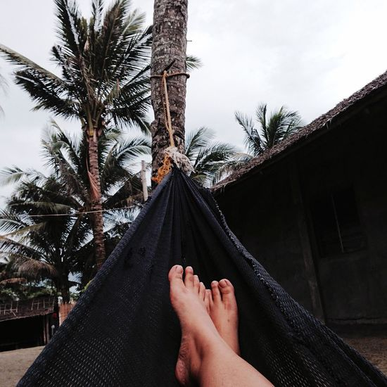 Low section of man on hammock against sky
