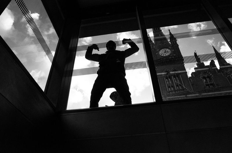 Low angle view of silhouette man standing by window at home