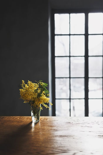 Close-up of vase on table against window
