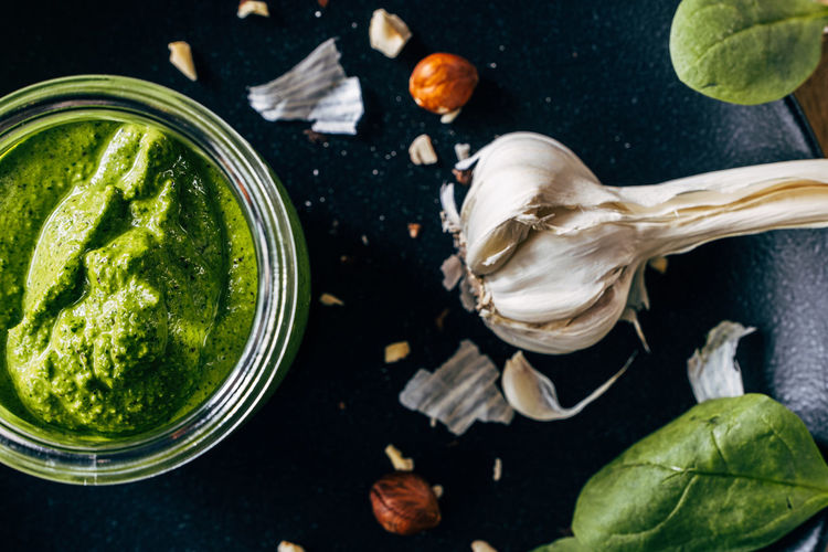 High angle view of pesto sauce in glass with garlic on table