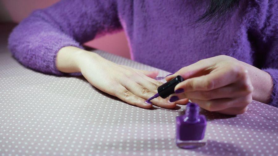 Close-up of woman applying nail polish