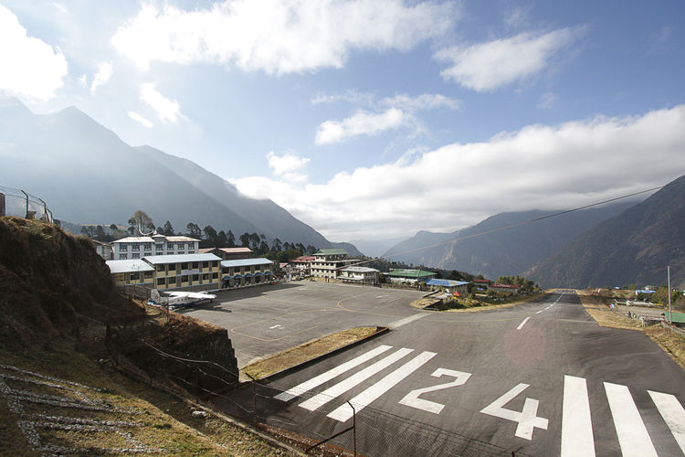 Lukla airport. One of the most dangerous airport in the world located in Everest region, Nepal Nature City Sky Sunlight Day Road Outdoors Sign Transportation Mountain Direction Himalayas Symbol Marking Aircraft Beauty In Nature No People Nepal Travel Lukla Airport Airport Runway Mountain Range The Way Forward Cloud - Sky Mode Of Transportation Scenics - Nature Road Marking Architecture