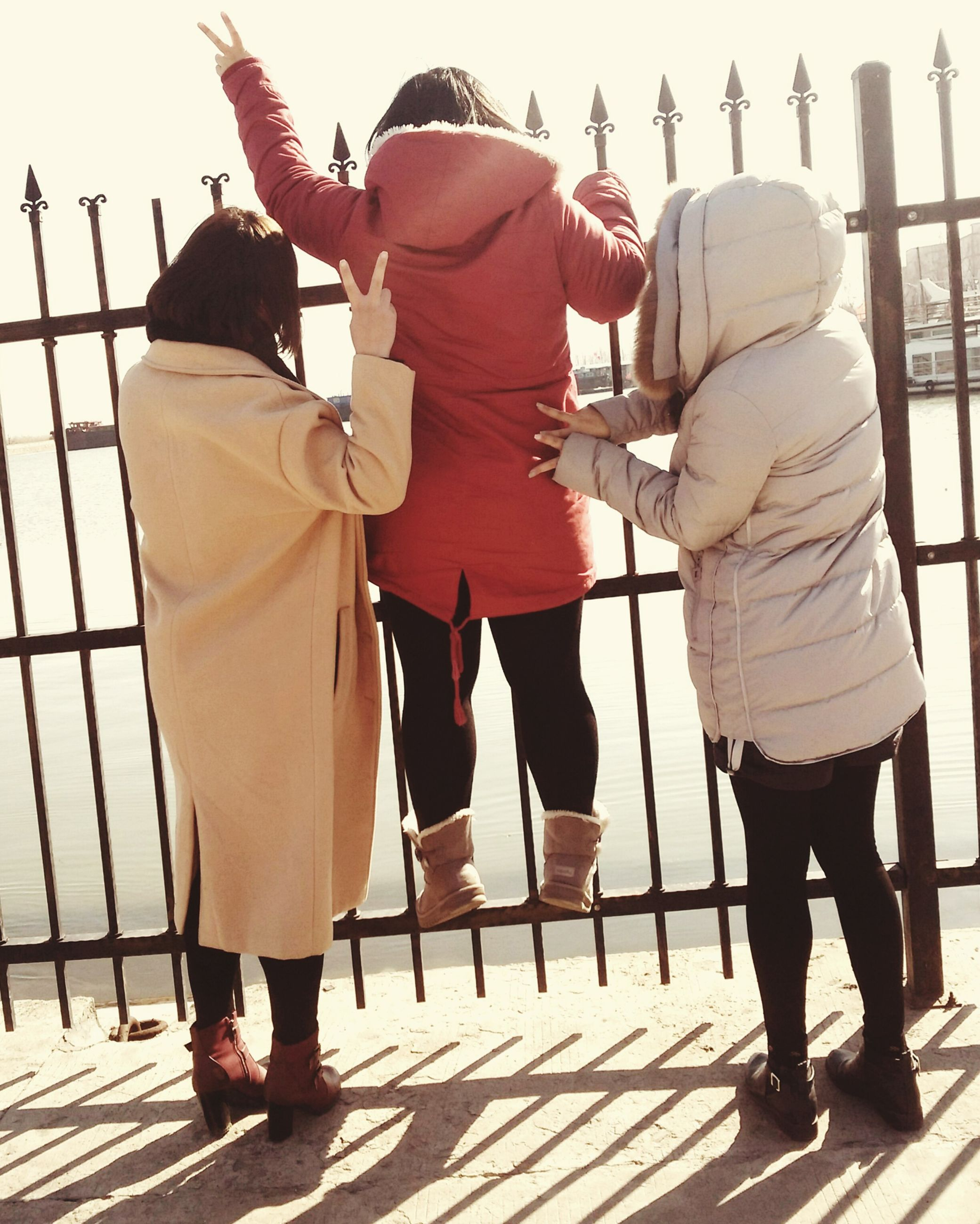 lifestyles, men, person, togetherness, rear view, leisure activity, casual clothing, full length, walking, standing, large group of people, bonding, medium group of people, side by side, love, in a row, railing, outdoors