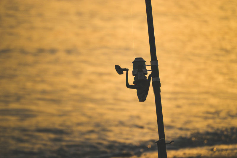 Close-up of silhouette fishing rod on pole