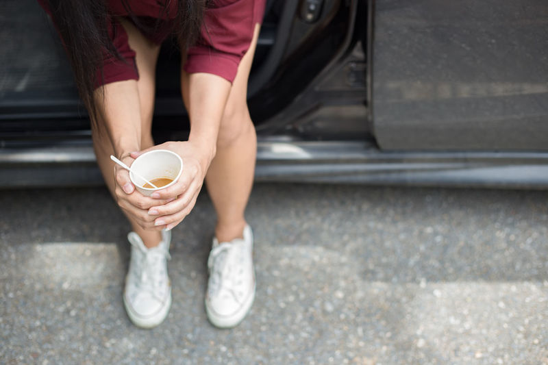 Woman sitting beside car and holding disposable cup of coffee Caffeine Close-up Coffee Day Espresso Human Hand Lifestyla Lifestyles Low Section One Person Outdoors Park Real People Sitting Standing Transportation Waiting