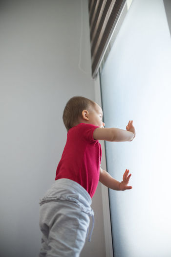 Side view of woman standing against wall at home
