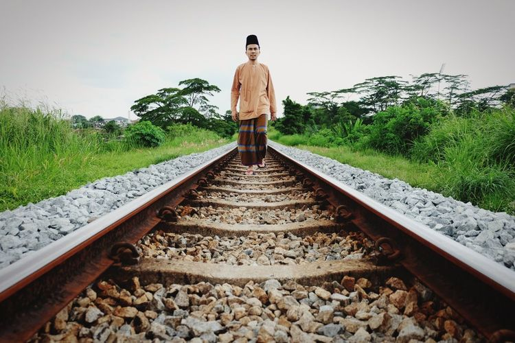 Full length of young man walking on railroad track against clear sky