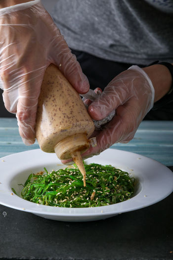 Close-up of person pouring green salad in plate on table