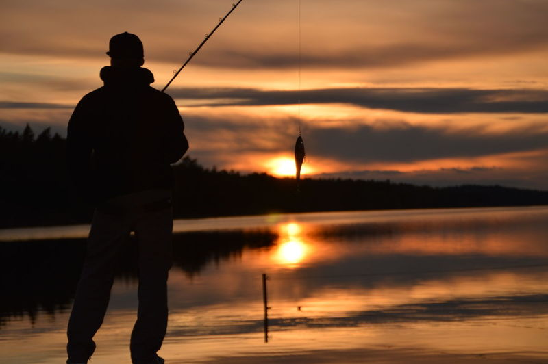 Silhouette man fishing on lake against sky during sunset