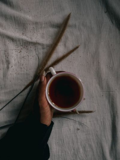 High angle view of hand holding tea cup on table