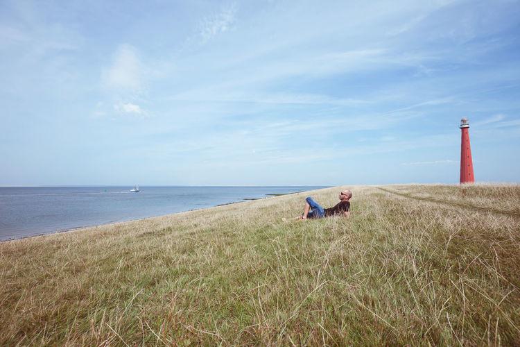 Man Relaxing At Beach Against Sky