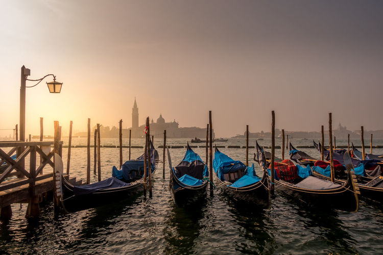 Gondolas moored at grand canal during sunset