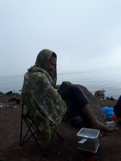 Man sitting by sea against clear sky