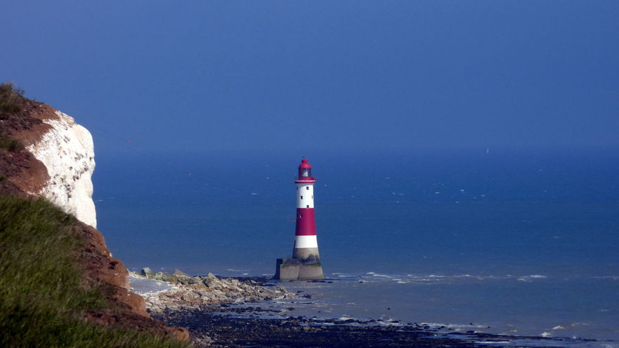 Lighthouse at sea shore against clear blue sky