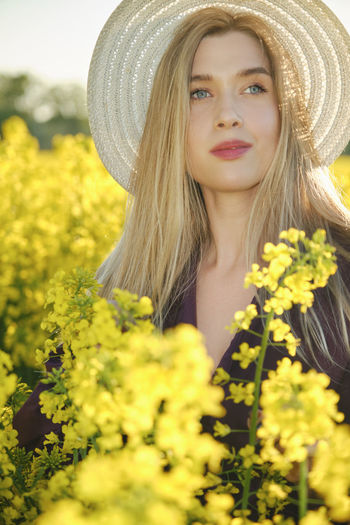 Portrait of beautiful young woman with yellow flowers