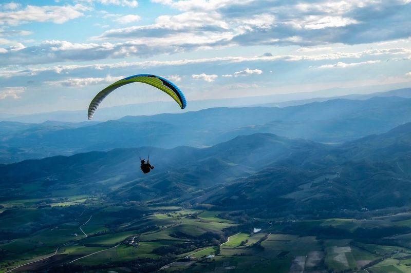 Scenic View Of Person Paragliding Against Sky