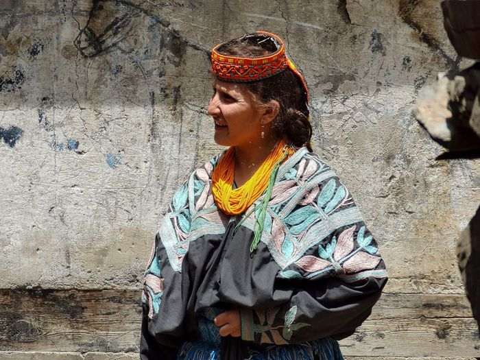 Woman in traditional clothes standing against wall