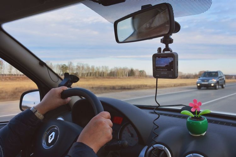 Driving in car Car Interior Transportation Mode Of Transport Land Vehicle Car Vehicle Interior Real People Steering Wheel Dashboard Windshield Human Hand Rear-view Mirror One Person Driving Sky Day Windscreen Leisure Activity Technology Close-up