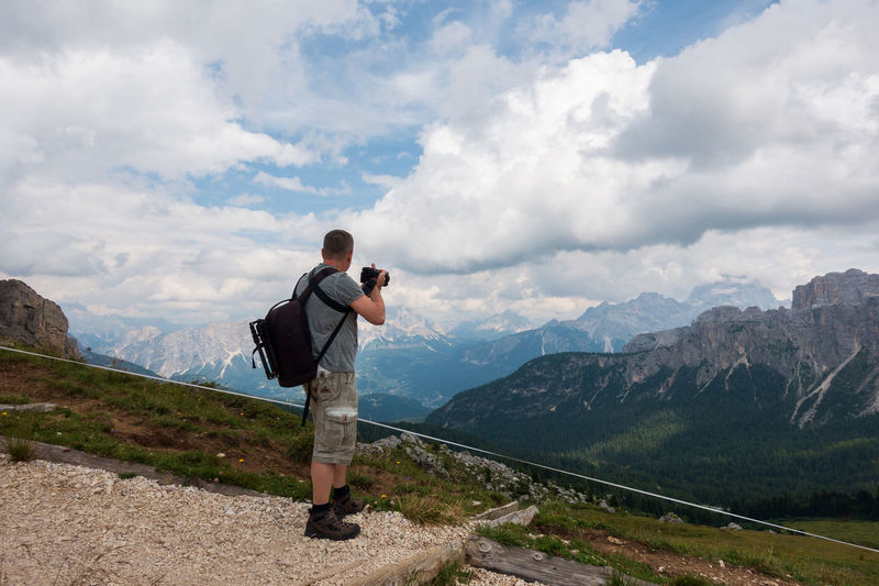 Side view of man standing on mountain against cloudy sky