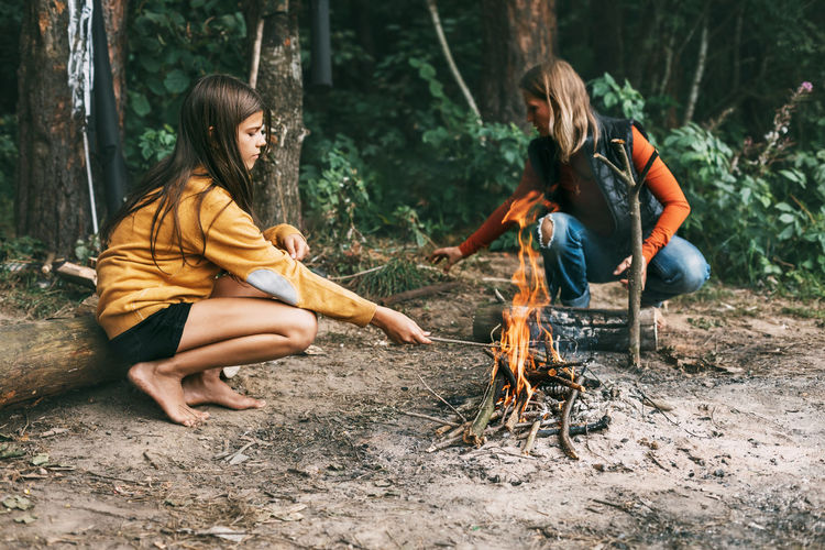 Full length of woman sitting on bonfire in forest