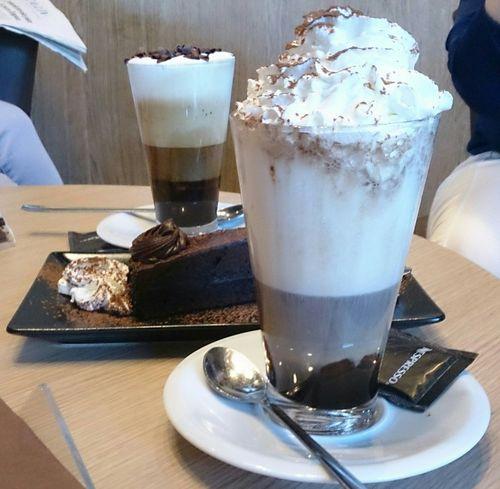 Tomandonos un señor Cafe con un trozo de Tarta De Chocolate en un Cafeteria de Nespresso