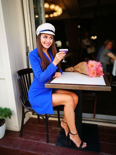 Young woman having drink while sitting at outdoor restaurant
