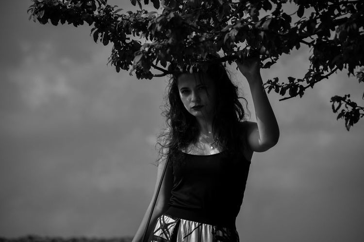 Portrait of woman standing by tree against sky