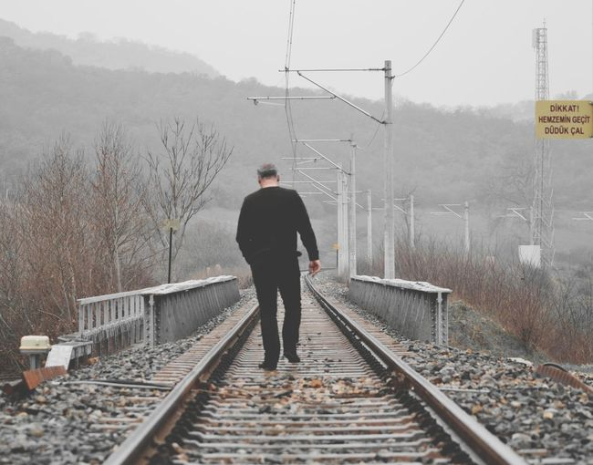 Rear view of man on railroad tracks during winter