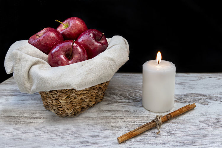 Healthy and organic red apples in a wicker basket and a stick cinnamon on black background with copy space Indoors  Studio Shot Candle Still Life Healthy Eating Food Freshness Flame No People Table Burning Fire Fruit Container Close-up Red Black Background Apple Red Organic Healthy Wicker Basket Cinnamon Copy Space Background Wallpaper Fresh Rustic Summer Diet Tasty Delicious Nutrition Agriculture Drops Water