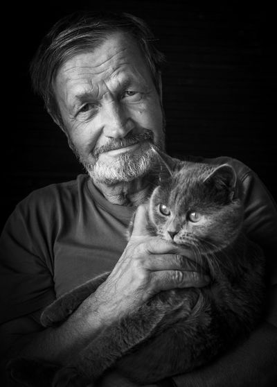 Portrait Of Man With Cat Against Black Background