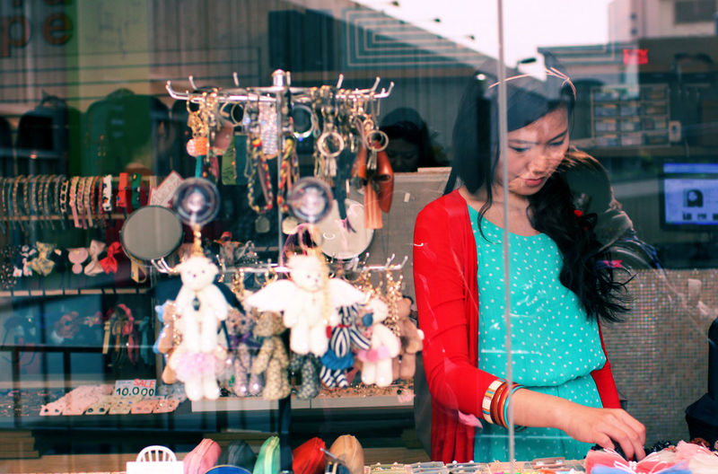Woman shopping while seen through window glass of store
