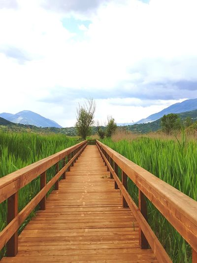 Surface level of wooden footbridge against sky
