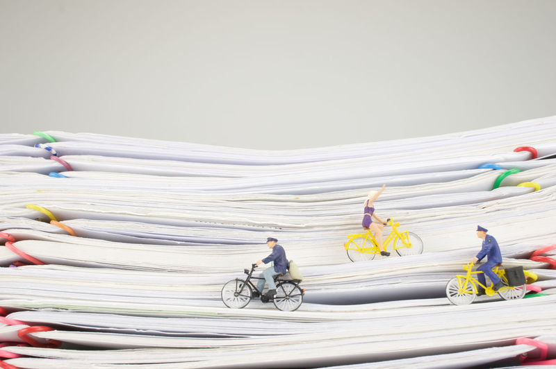 Figurines with toy bicycles on stacked papers