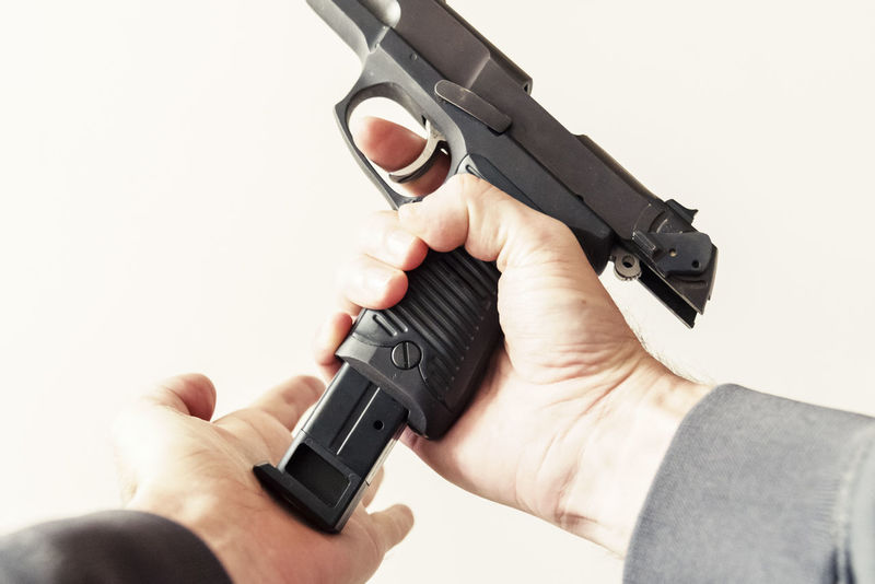 Point of view personal perspective loading a clip into a handgun weapon. Crime Gang Close-up Criminal Gun Handgun High Angle View Holding Human Body Part Human Hand Law Enforcement Men Military One Person Personal Perspective Point Of View Police Real People Shooting Studio Shot Terrorism Violence War Weapon White Background