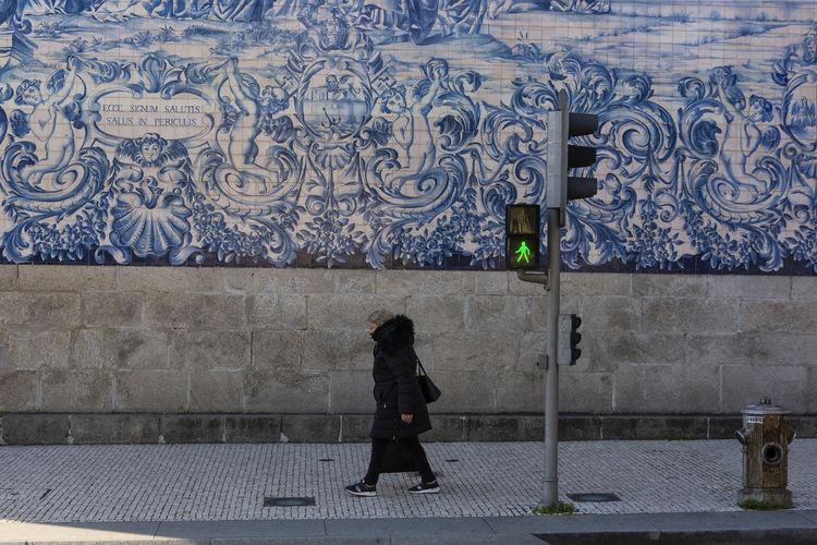 Full length rear view of woman walking on footpath
