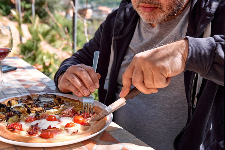 Man cutting pizza in the plate on tile table in the garden. homemade italian pizza.