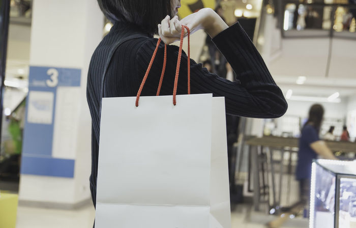 Young Asian woman holding shopping bag in shopping mall. Shopping concept. Women Rear View Focus On Foreground Real People Standing One Person Indoors  Adult Incidental People Midsection Lifestyles Education Casual Clothing Leisure Activity Day Hairstyle Hair Holding Occupation