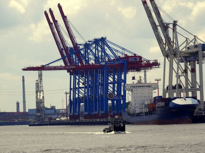 Low angle view of cranes by river against sky on sunny day at harbor