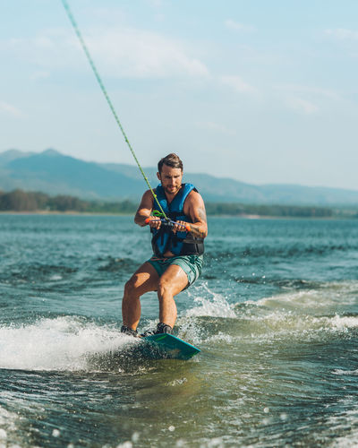 Full length of wakeboarding in sea