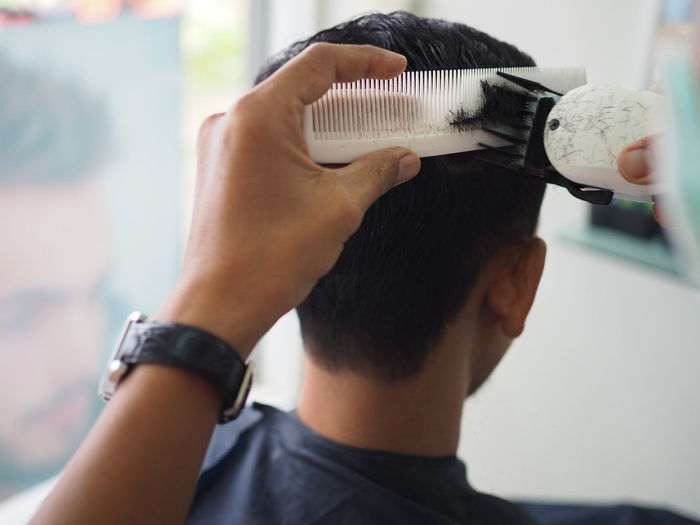 Cropped image of barber cutting hair of customer