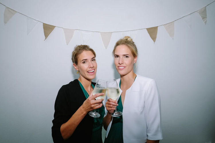 Portrait of twin sisters toasting wineglasses against wall